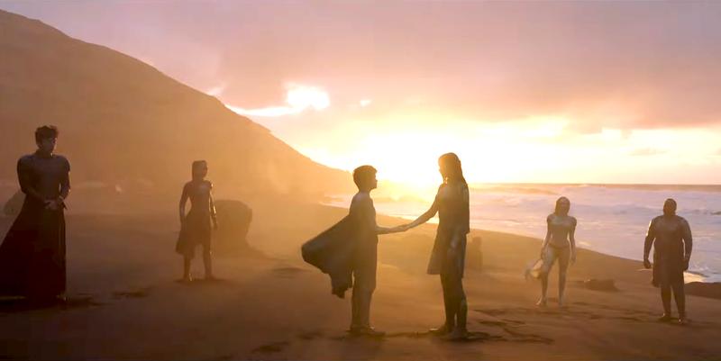 The Eternals standing on a beach