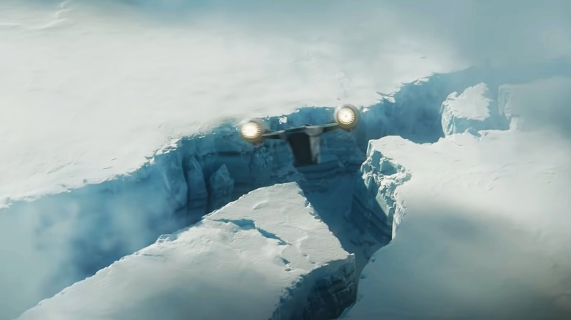 The Razor Crest flying towards a trench of snow