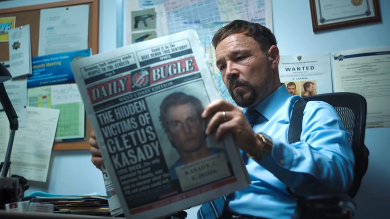 A police officer reading a copy of the Daily Bugle